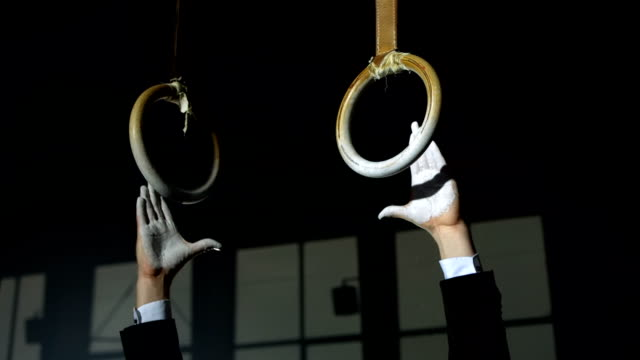 hd super slow-mo: businessman gripping gymnastics rings - gymnastic rings stock videos & royalty-free footage
