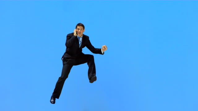 HD Super Slow-Mo: Businessman Jumping And Talking On The Phone