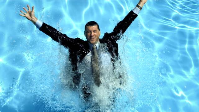 hd super slow-mo: businessman splashing into the pool - kostym bildbanksvideor och videomaterial från bakom kulisserna