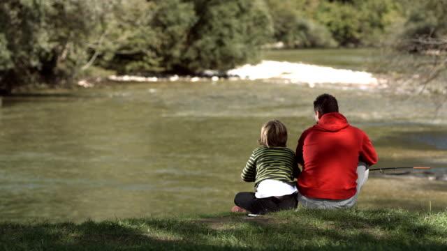 hd super slow-mo: cheerful father and son fishing - fisher role stock videos & royalty-free footage