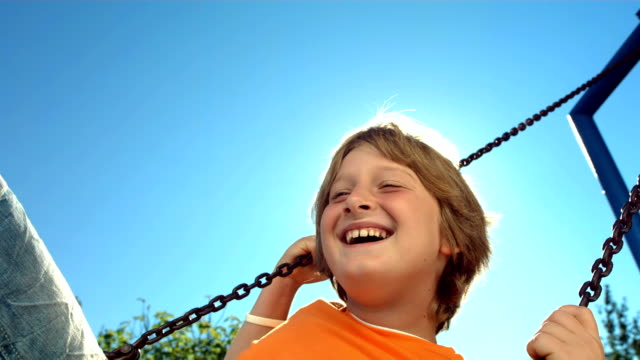 hd super slow-mo: cheerful little boy swinging - playground stock videos & royalty-free footage