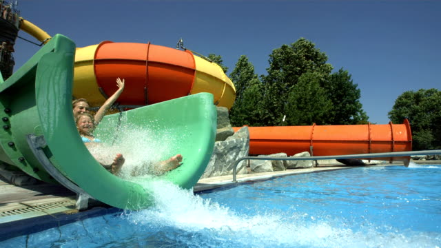 hd super slow-mo: cheerful mother and daughter in water park - water slide stock videos & royalty-free footage