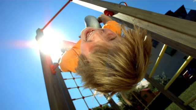 stockvideo's en b-roll-footage met hd super slow-mo: child hanging from jungle gym - speeltuin