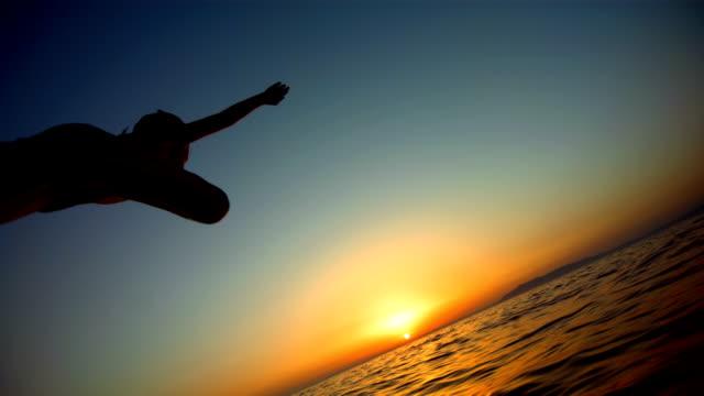 stockvideo's en b-roll-footage met hd super slow-mo: child jumping in the sea - avondschemering