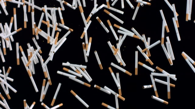 hd super slow-mo: cigarettes falling over black background - cigarette stock videos & royalty-free footage