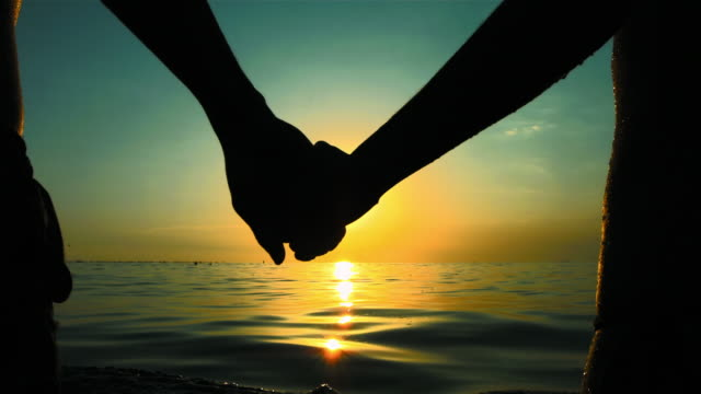 hd super slow-mo: couple holding hands in the sea - flirting stock videos & royalty-free footage