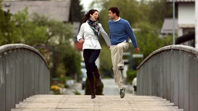 hd super slow-mo: couple hopping across bridge - mid adult couple stock videos & royalty-free footage