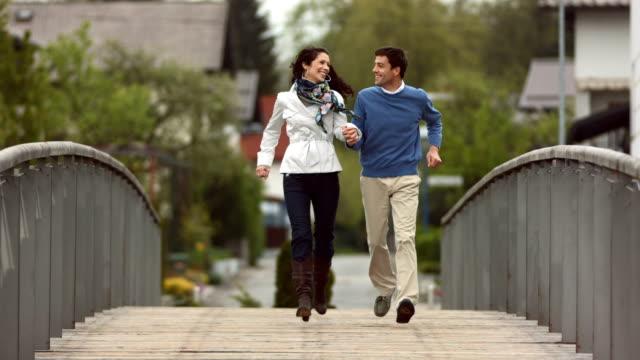 HD Super Slow-Mo: Couple Running Across Bridge