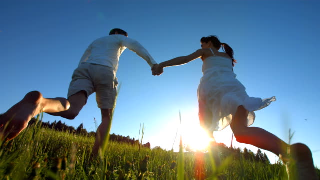 HD Super Slow-Mo: Couple Running In Grass At Sunset