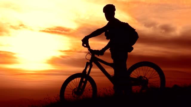 vídeos de stock, filmes e b-roll de super câmera hd-seg: cycler desfrutando da vista do pôr-do-sol - imagem tonalizada