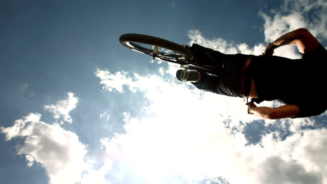 hd super slow-mo: dirt backflipping against cloudy sky - bmx cycling stock videos and b-roll footage