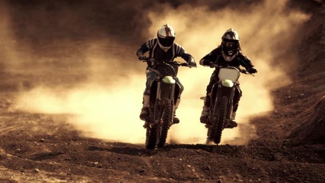 vídeos de stock e filmes b-roll de super slow-mo: dirt bikers riding at dusk - enfeites para a cabeça