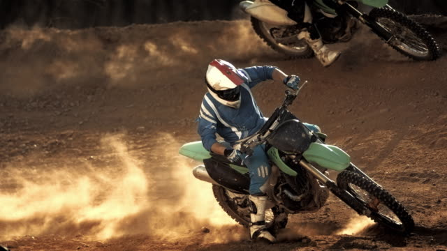 super slow-mo: dirt bikers speeding at apex turn - motorcycle racing stock videos and b-roll footage