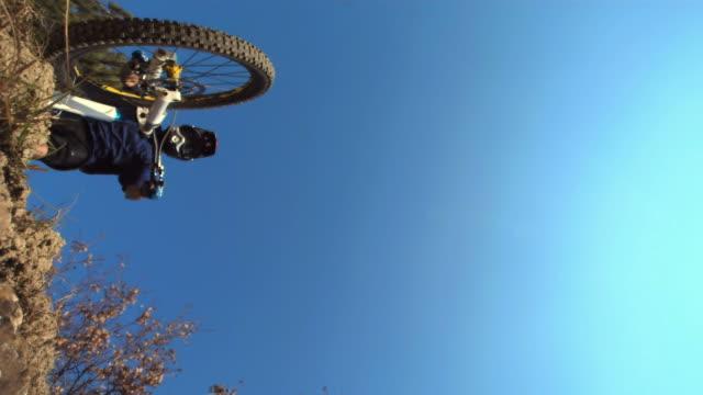 hd 超スローモーション: ダウンヒルバイカージャンプオフロック - スタントバイク点の映像素材/bロール