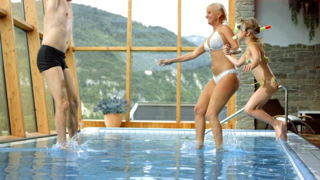 vídeos de stock, filmes e b-roll de super câmera hd-seg: família se divertindo pulando na piscina - família de um filho