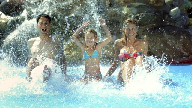 hd super slow-motion: famiglia divertirsi spruzzi d'acqua - acquascivolo video stock e b–roll