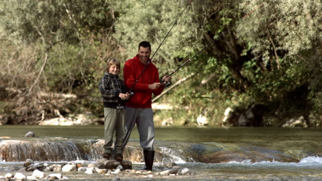 hd super slow-mo: father and son enjoys fishing - recreational pursuit stock videos & royalty-free footage
