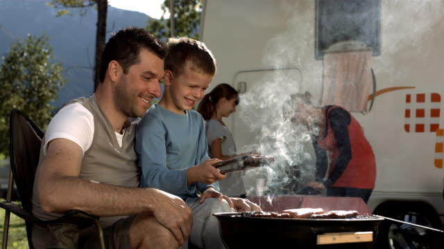 hd super slow-mo: father and son grilling meat on barbecue - grilled stock videos and b-roll footage