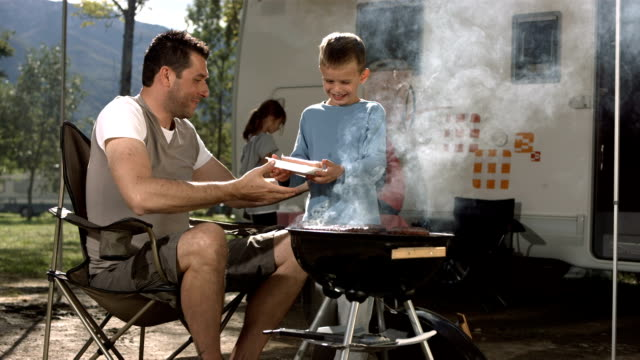 HD Super Slow-Mo: Father And Son Grilling Meat On Barbecue