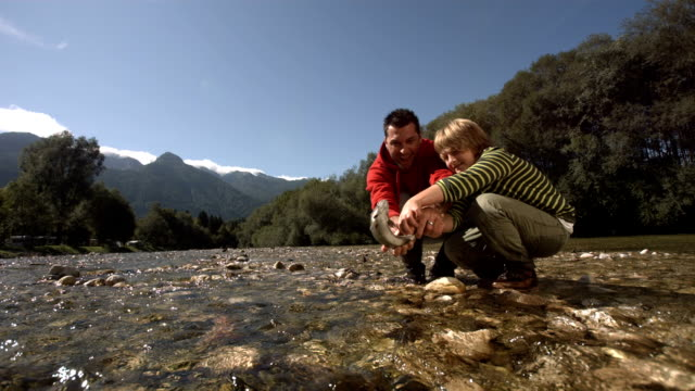 HD Super Slow-Mo: Father And Son Releasing The Fish