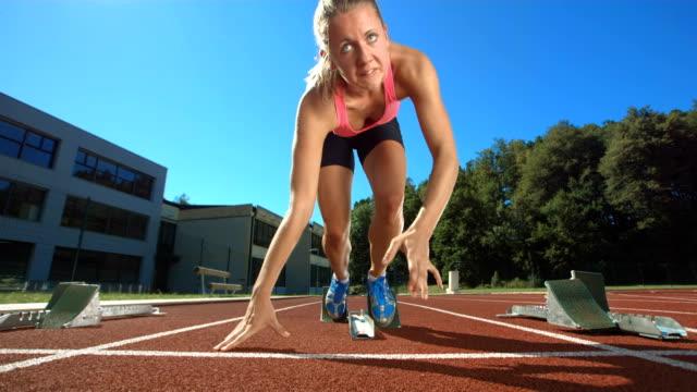 hd super slow-motion: donna corridore a partire da - blocco di partenza per l'atletica video stock e b–roll