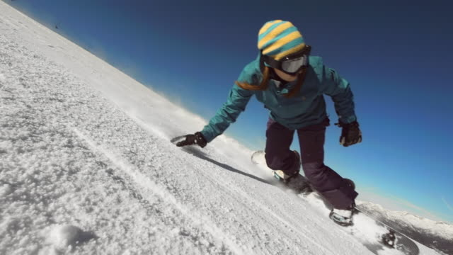 vídeos de stock e filmes b-roll de super slow-mo: female snowboarder carving down ski slope - roupa de esqui