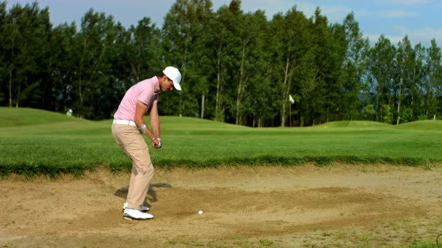 hd super slow-mo: golfer making a bunker shot - golf swing stock videos & royalty-free footage