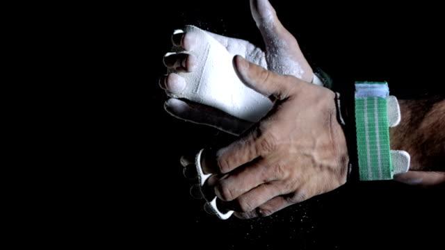 vídeos y material grabado en eventos de stock de hd super cámara lenta: gimnasta chalking las manos - magnesio