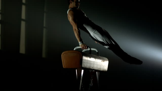stockvideo's en b-roll-footage met hd super slow-mo: gymnast swings on the pommel horse - gym