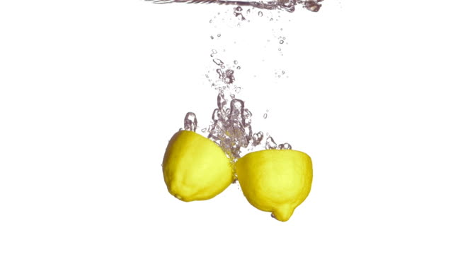 hd super slow-mo: half cut lemons splashing into water - lemon stock videos & royalty-free footage
