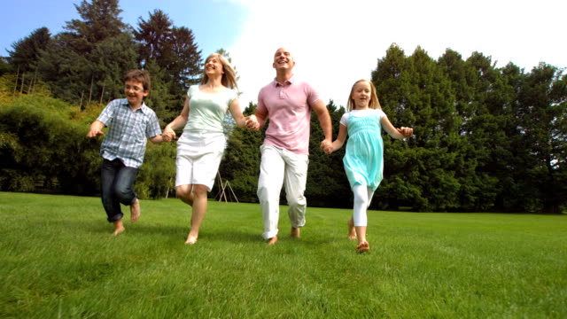 HD Super Slow-Mo: Happy Family Running On The Lawn