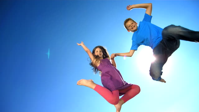 hd super slow-mo: happy siblings jumping in the air - jumping stock videos & royalty-free footage