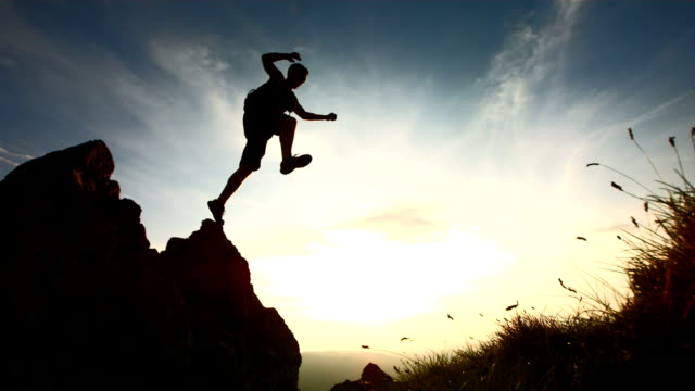 hd super slow-mo: hiker jumping from a rock - silhouette stock videos & royalty-free footage