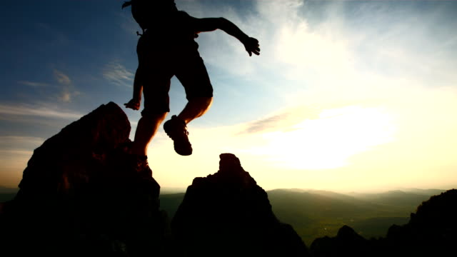 stockvideo's en b-roll-footage met hd super slow-mo: hiker jumping over rocks at dusk - exploratie