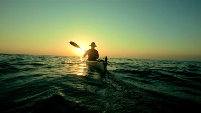 hd super slow-motion: kayak in mare al tramonto - pagaiare video stock e b–roll