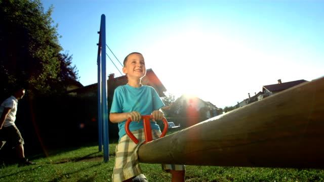 vídeos y material grabado en eventos de stock de hd super cámara lenta: los niños se divierten en un patio de juegos - balancín