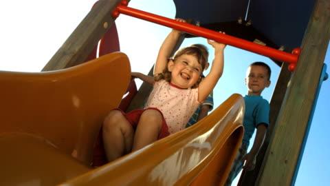 hd super slow-mo: kids having fun sliding on a slide - sliding stock videos & royalty-free footage