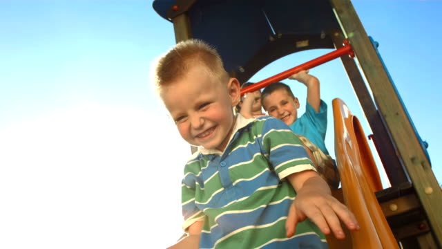 hd super slow-mo: kids sliding on a slide - playground stock videos & royalty-free footage