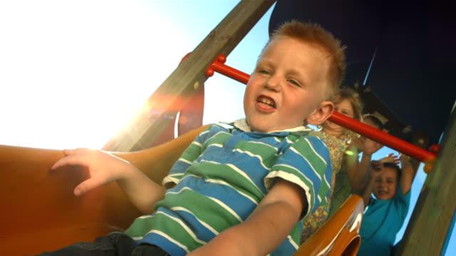 vídeos de stock, filmes e b-roll de super câmera hd-seg: menino de correr a um slide - deslizar