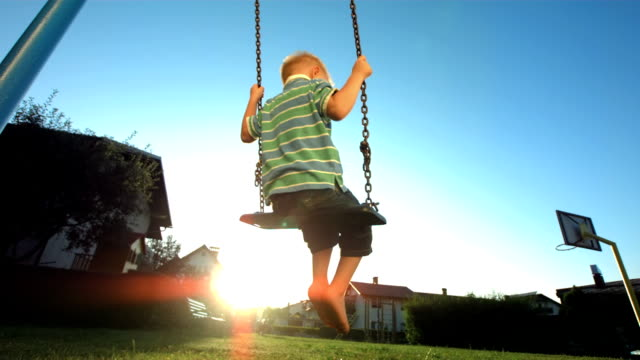 hd super slow-mo: little boy swinging against sunny sky - swinging stock videos & royalty-free footage