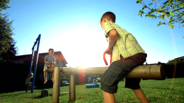 hd super slow-mo: little boys playing on a seesaw - swing stock videos and b-roll footage