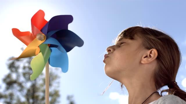 vidéos et rushes de hd super slow-motion: petite fille souffler un moulin à vent - souffler