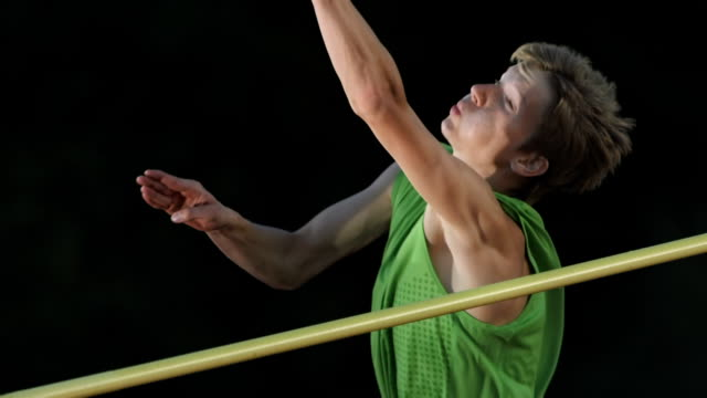 hd super slow-mo: male athlete jumping over a horizontal bar - horizontal bar stock videos and b-roll footage
