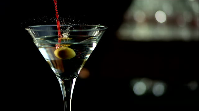 hd super slow-mo: martini with an olive garnish - martini stock videos & royalty-free footage