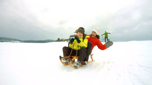HD Super Slow-Mo: Mother And Son Sledging Down The Hill