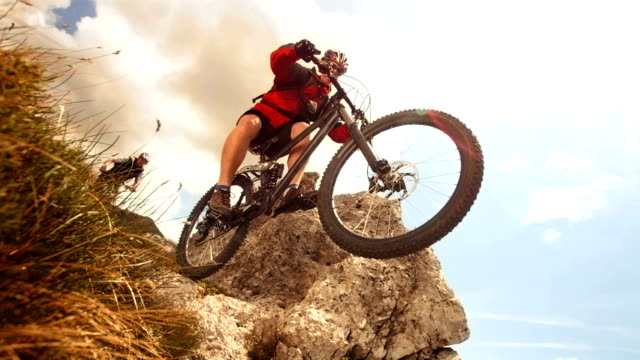 hd super slow-motion: ciclista di mountain bike e saltare su roccia - andare in mountain bike video stock e b–roll