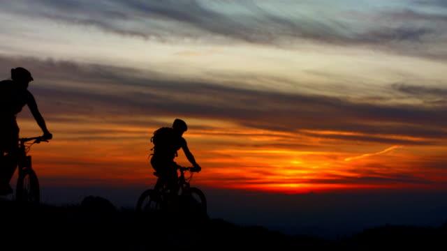 vídeos y material grabado en eventos de stock de hd super cámara lenta: ciclistas de montaña riding al atardecer - mountain bike