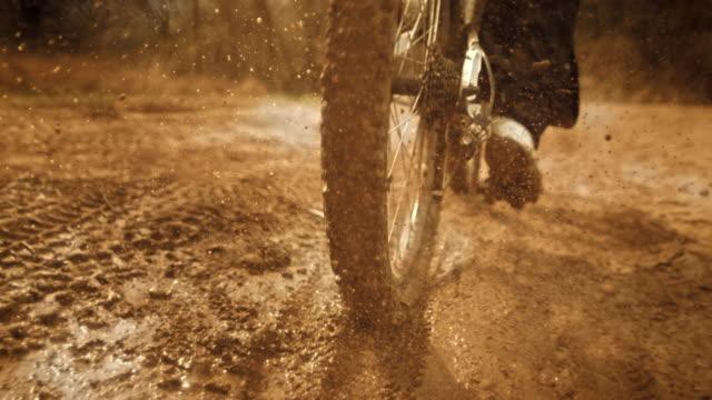 vídeos de stock, filmes e b-roll de super slow-mo: mtb motociclista chutar lama na câmera - montar um animal