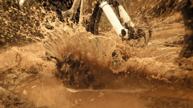 hd super slow-motion: mtb motociclista si increspa fango alla macchina fotografica - mountain bike video stock e b–roll