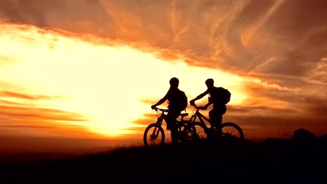 vídeos de stock, filmes e b-roll de super câmera hd-seg: mtb cyclers desfrutando da vista do pôr-do-sol - imagem tonalizada